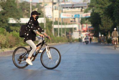 Mitglied von Drop and Ride mit Maske auf dem Fahrrad in Kabul
