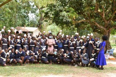 Gruppe von Schulmädchen aus Kenia, die lachend Binden in den Händen halten